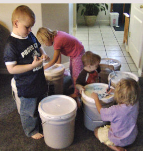 Kids marking foods storage buckets